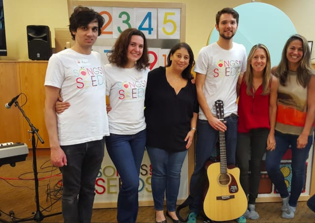 Dana Fisher, in middle in black blouse, with band and Songs for Seeds NYC founders.